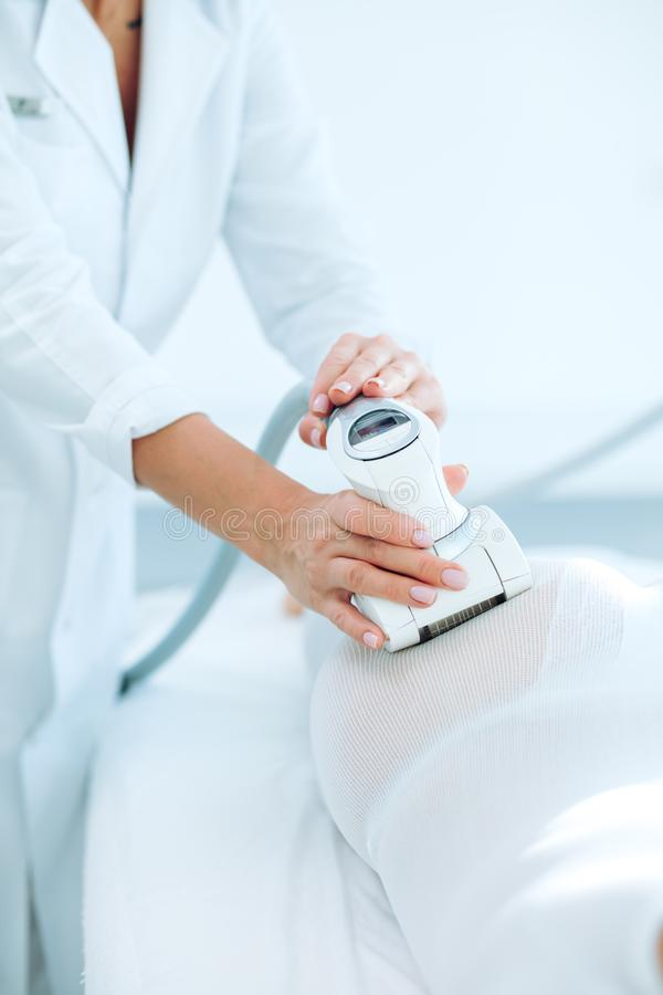 Woman in white suit getting LPG procedure , body contouring treatment in clinic. royalty free stock photo