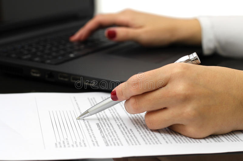 Close up of female business hands working on document and lapto royalty free stock photos