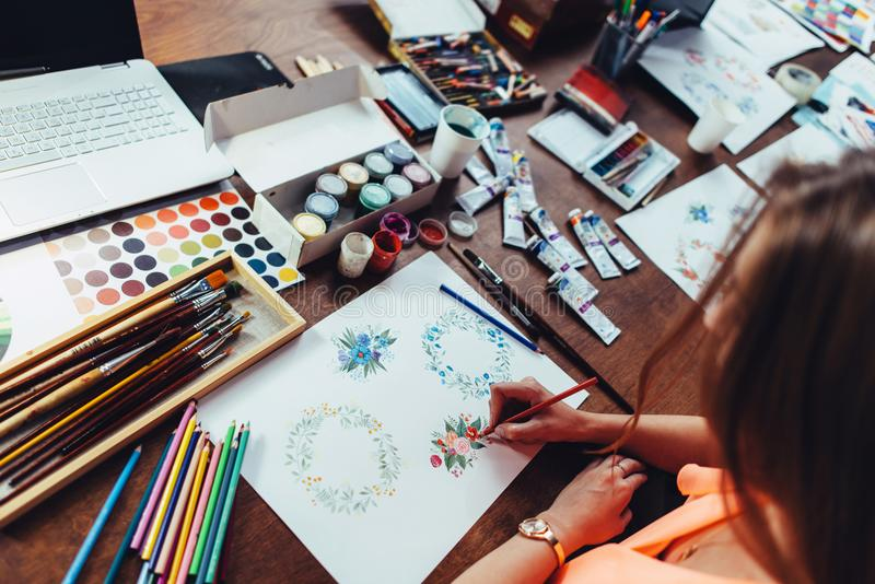 Close-up of female designer drawing floral compositions with crayons sitting at workplace surrounded with paint, gouache stock photos