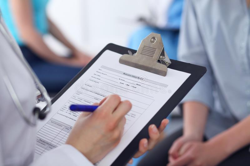 Close Up of a female doctor filling out application form while talking to patient. Medicine and health care concept royalty free stock images