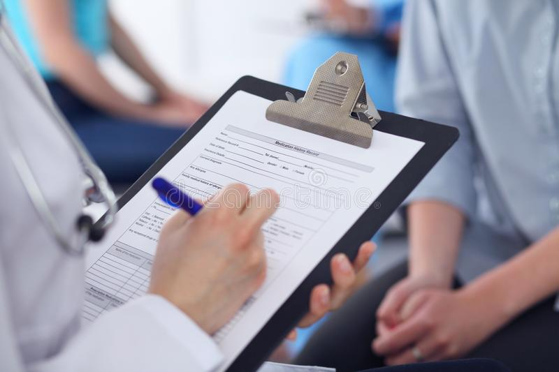 Close Up of a female doctor filling out application form while talking to patient. Medicine and health care concept royalty free stock photo