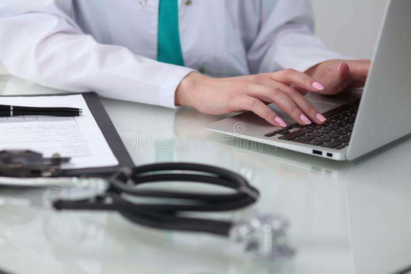 Close-up of female doctor hands typing on laptop computer. Physician at work. Medicine, healthcare and help concept royalty free stock images