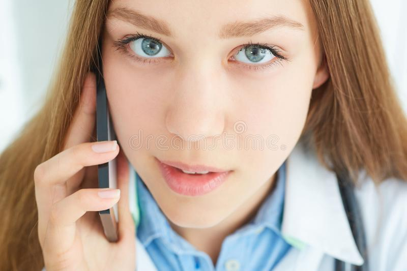 Young girl doctor talking on the phone looking at the camera. Close up female doctor having phone call in medical office stock images