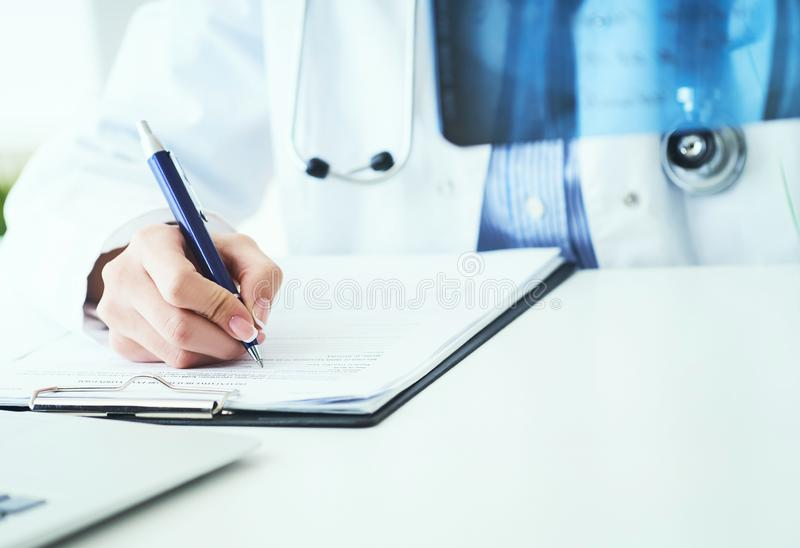 Close up of female doctor holding x-ray or roentgen image and making notes in medical form. Female doctor holding x-ray or roentgen image and making notes in stock image