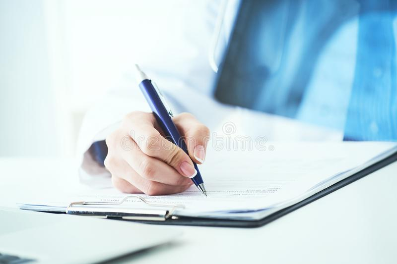 Close up of female doctor holding x-ray or roentgen image and making notes in medical form. Female doctor holding x-ray or roentgen image and making notes in royalty free stock photography
