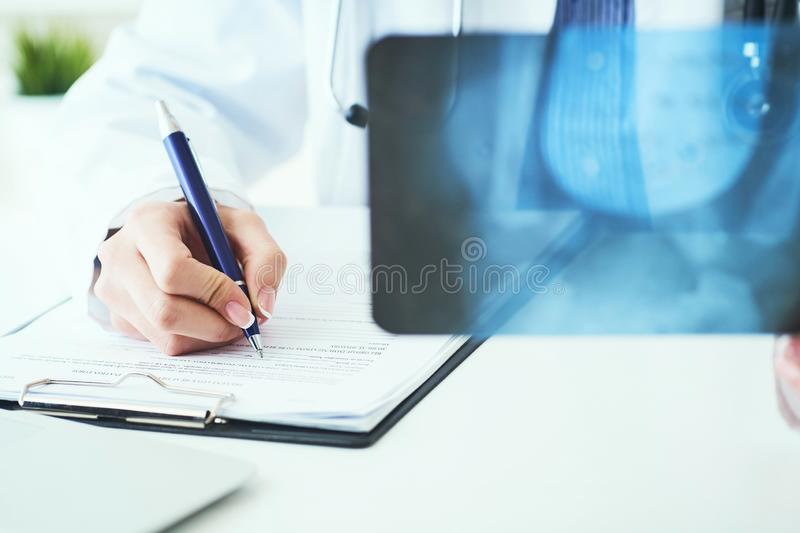 Close up of female doctor holding x-ray or roentgen image and making notes in medical form. Female doctor holding x-ray or roentgen image and making notes in royalty free stock image
