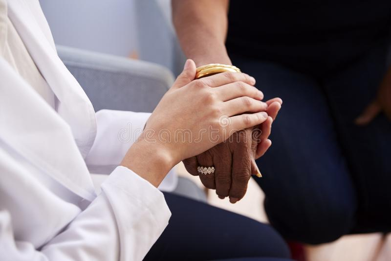 Close Up Of Female Doctor In Office Reassuring Senior Woman Patient And Holding Her Hands royalty free stock photography