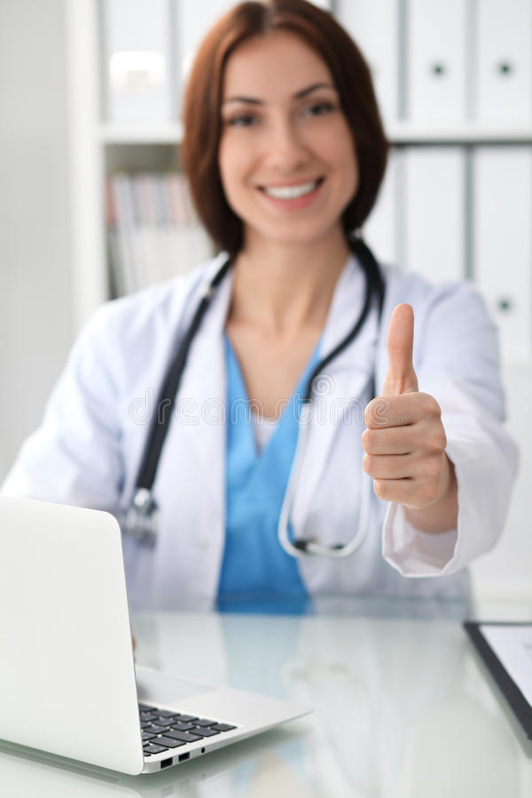 Close up of female doctor thumbs up. Happy cheerful smiling brunette physician ready to examine patient. Medicine royalty free stock photos