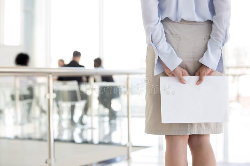 Close up of female employee feel nervous before speech making. Close up of female employee standing in hallway holding documents, feeling worried before entering stock photos
