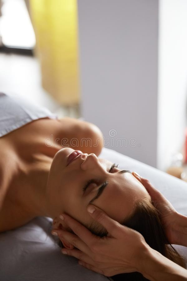 Head and face massage in spa salon stock photos