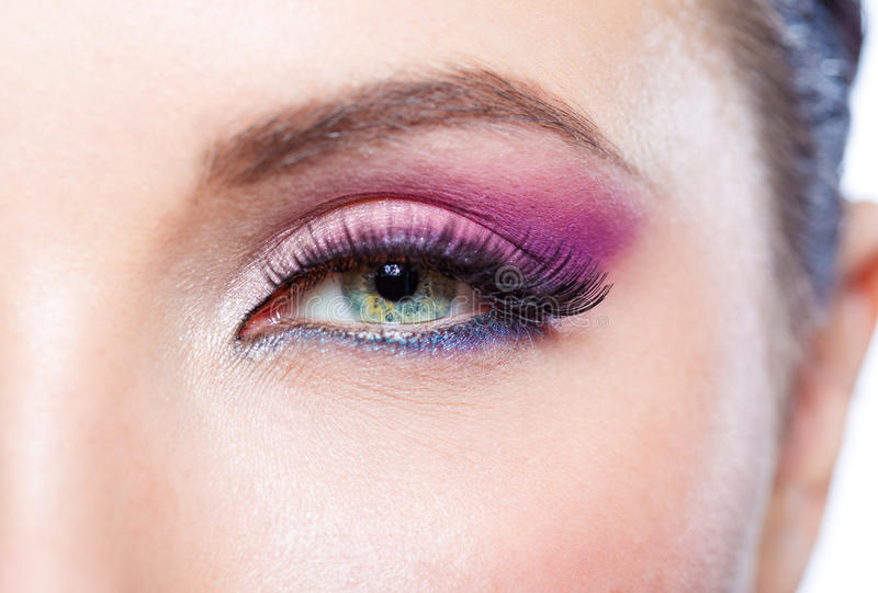 Close up of female eye with bright pink makeup. Concept of beauty and fashion stock photos
