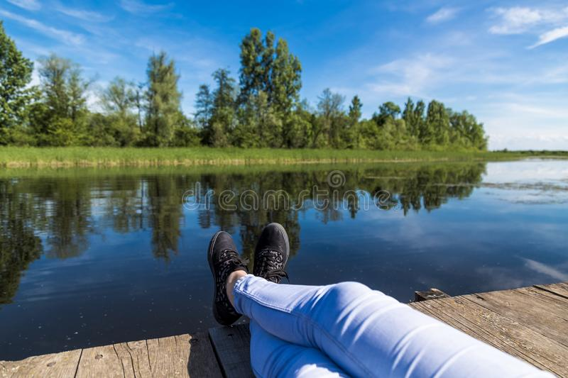 Woman feet against beautiful lake. Spring or summer vacation traveling concept royalty free stock photography