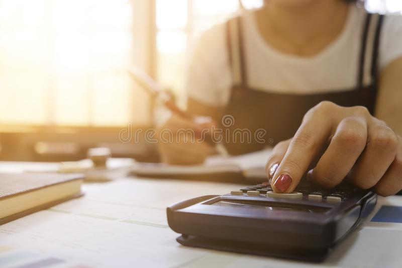 Close up of female Hand doing finances and calculate on desk about cost at home office. accountant or banker making calculations. stock image