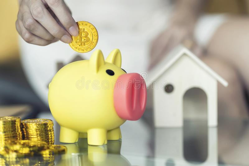 Close up, Female hand holding bitcoin and putting coin into yellow piggy bank. Save money concepts stock photos