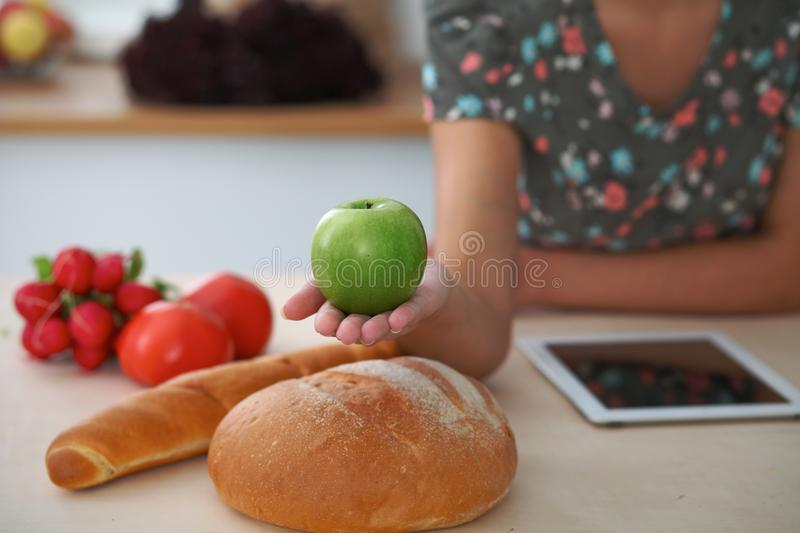 Close-up of female hand holding green apple in kitchen interiors. Many vegetables and other meal at glass table are stock images