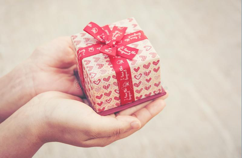 Close up female hand holding a small gift heart pattern. With re royalty free stock photo