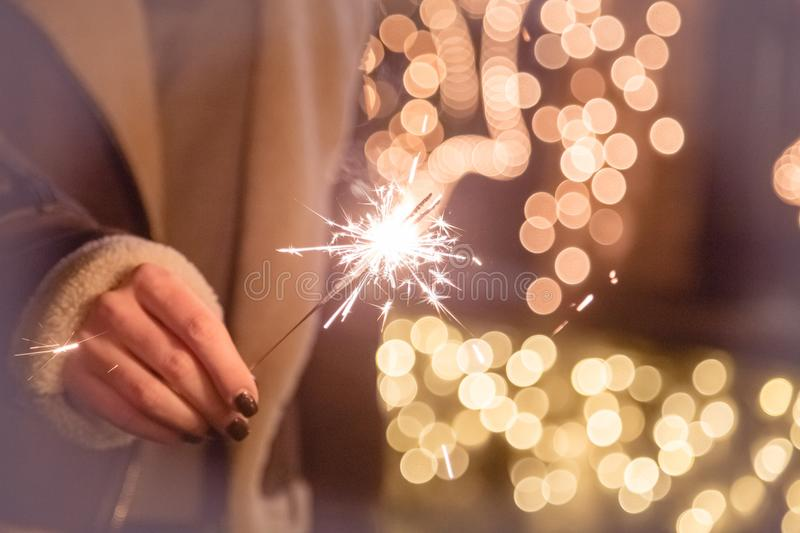 Close up of female hand holding sparkler against bokeh backgroun royalty free stock photo