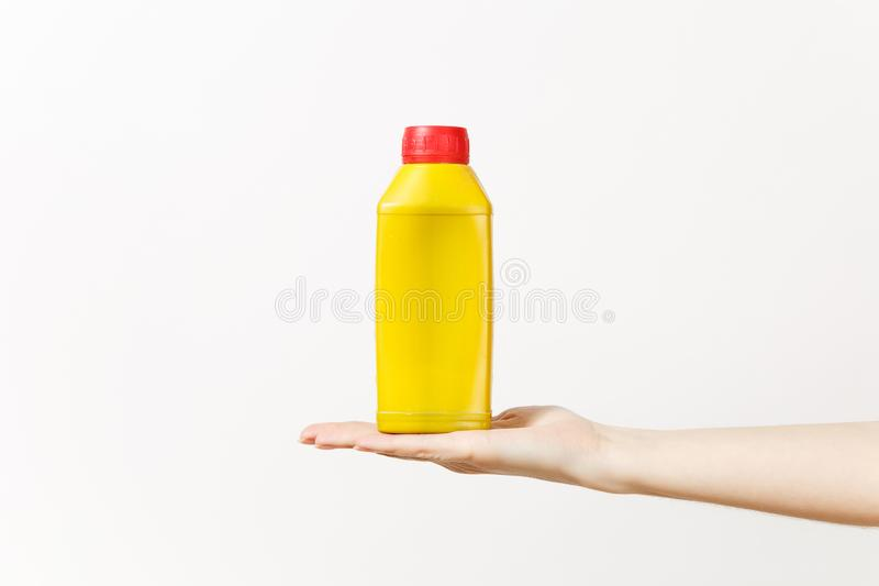 Close up of female hand horizontal holds yellow empty blank bottle with copy space isolated on white background stock image
