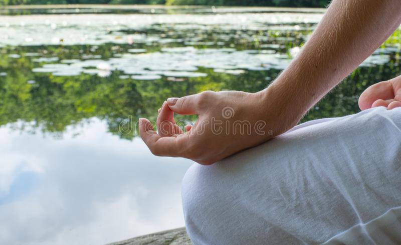 Close-up female hand in lotus position. Woman practicing yoga and meditating stock photography