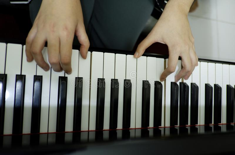 Close-up female hand playing grand piano stock images