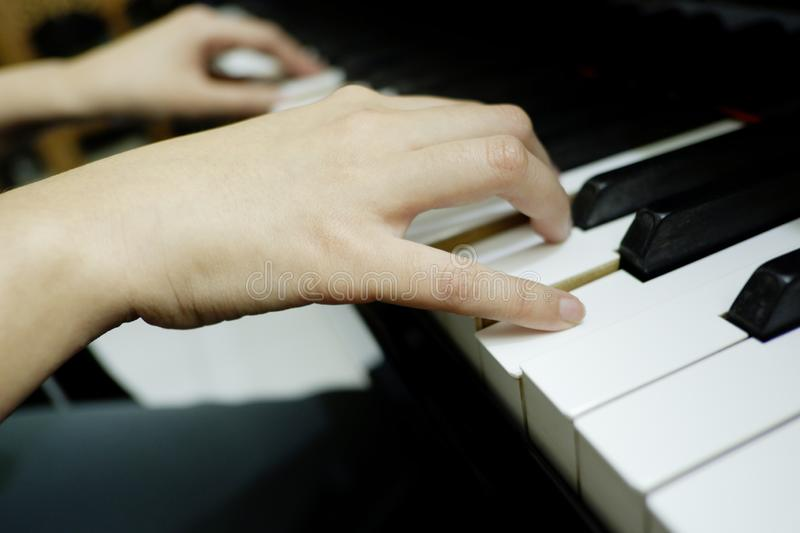 Close-up female hand playing grand piano royalty free stock photography