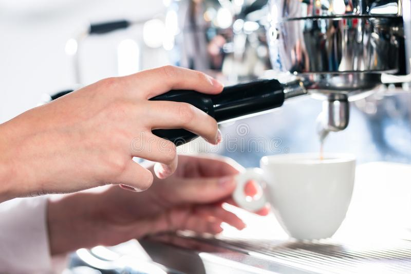 Close-up of female hand on the portafilter of an automatic coffe royalty free stock image