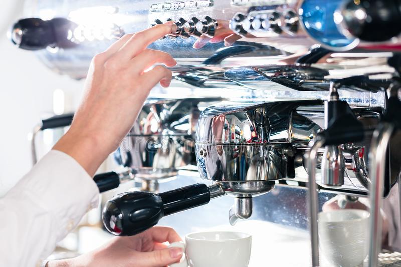 Close-up of female hand on the portafilter of an automatic coffe stock photography
