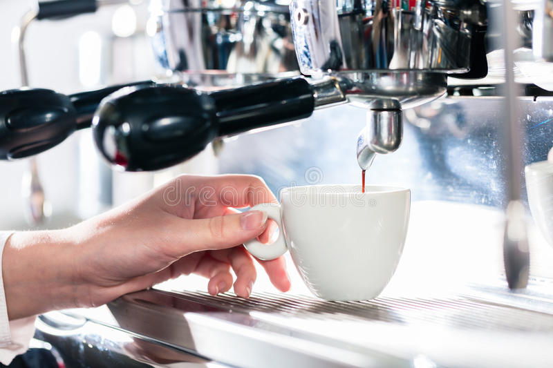 Close-up of female hand on the portafilter of an automatic coffe stock images