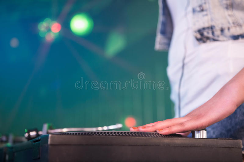 Close-up of a female hand on a record. Close-up of a female DJ hand on a record at nightclub royalty free stock photography