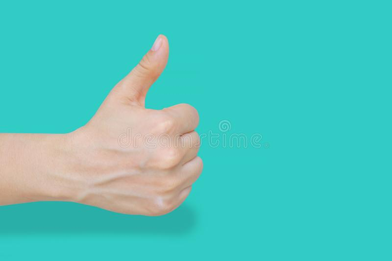 Close up of female hand showing thumbs up gesture over blue pastel background with clipping path. Body language that says ok, all. Right, good and like sign royalty free stock image