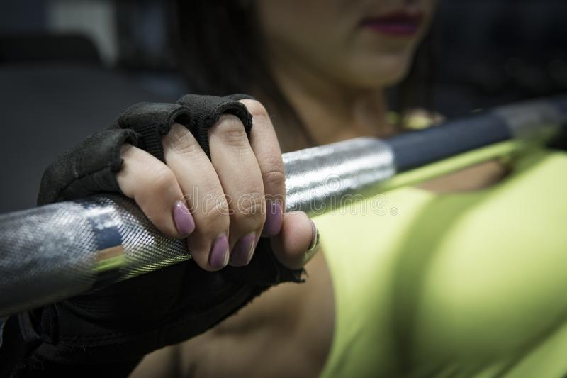 Close up of female hand in wrist wrap holding steel barbell. Manicured fingers of a sportswoman lying on bench in gym royalty free stock images