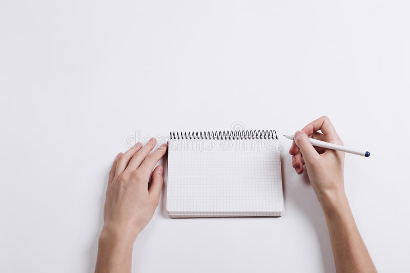 Close-up of female hand writing pen in a blank notebook royalty free stock image