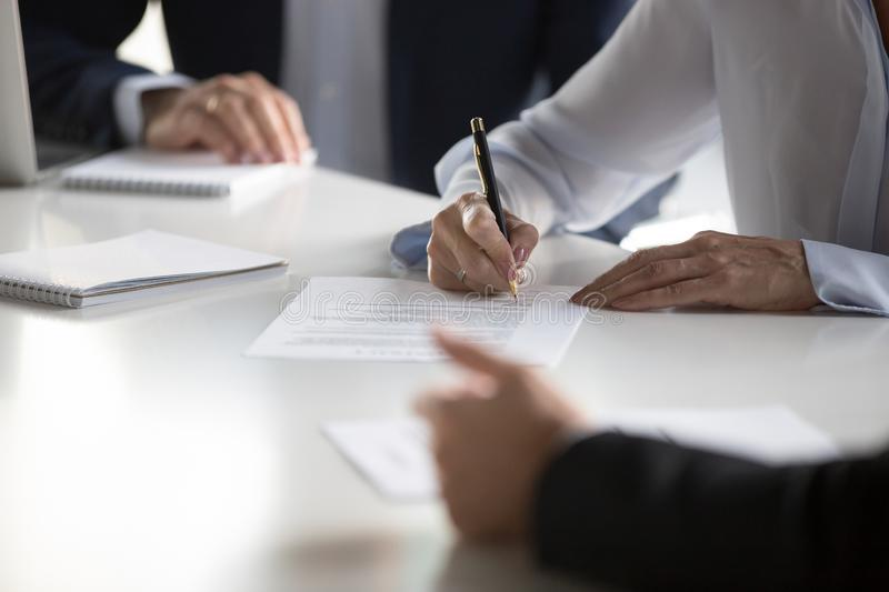 Close up female hands affirming contract with signature during m stock image