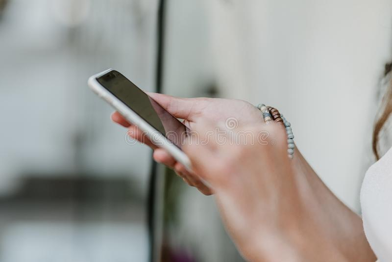 Close up Female hands with bracelets holding smartphone. Woman hand holding mobile phone. Communication, internet, white, media, wireless, modern, application royalty free stock photo