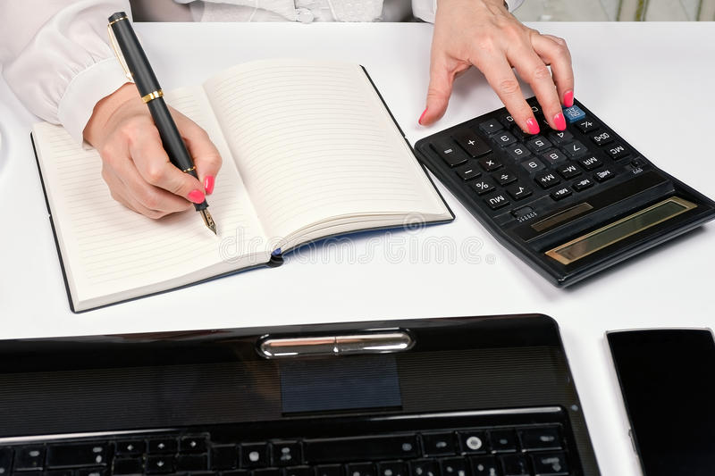 Close-up of female hands with calculator, fountain pen and notebook royalty free stock image