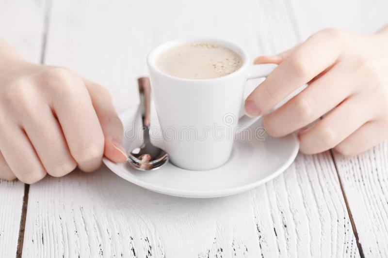 Close up female hands with cup of coffee on the table. coffee break closeup stock photos
