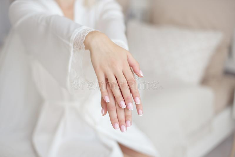 Close-up female hands in focus with blurred slim waist body on background. stock photography