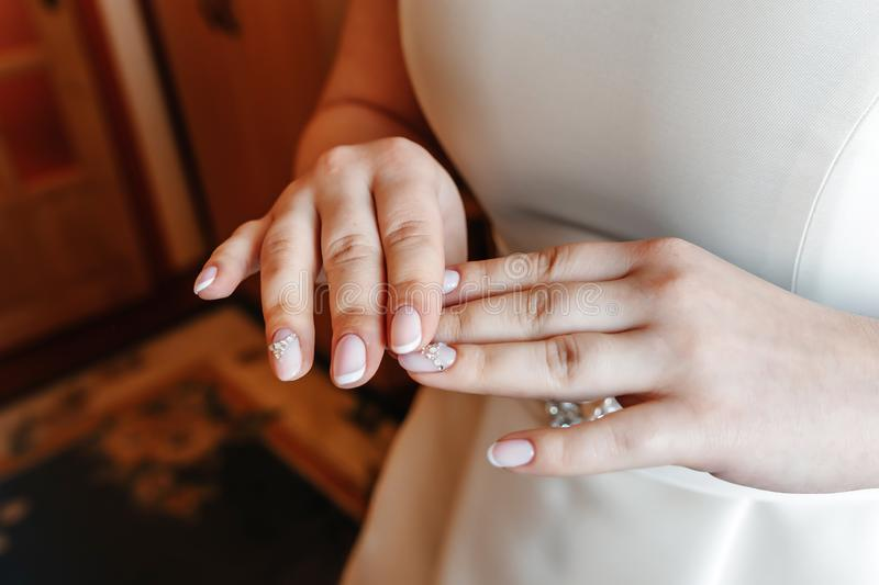 Close-up female hands in focus with blurred slim waist body on background. Woman wearing in wedding dress holding her hands in royalty free stock image
