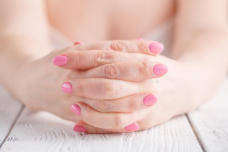 Close up on female hands folded in prayer at a wooden table stock photos