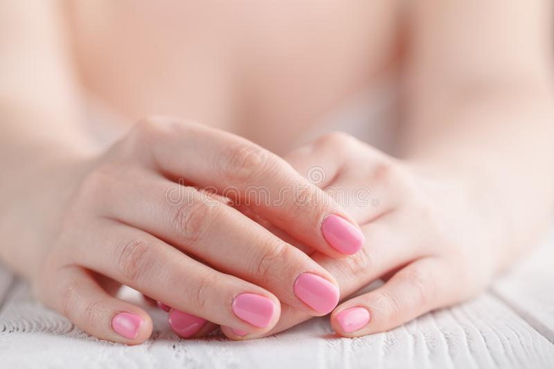 Close up on female hands folded in prayer at a wooden table royalty free stock images