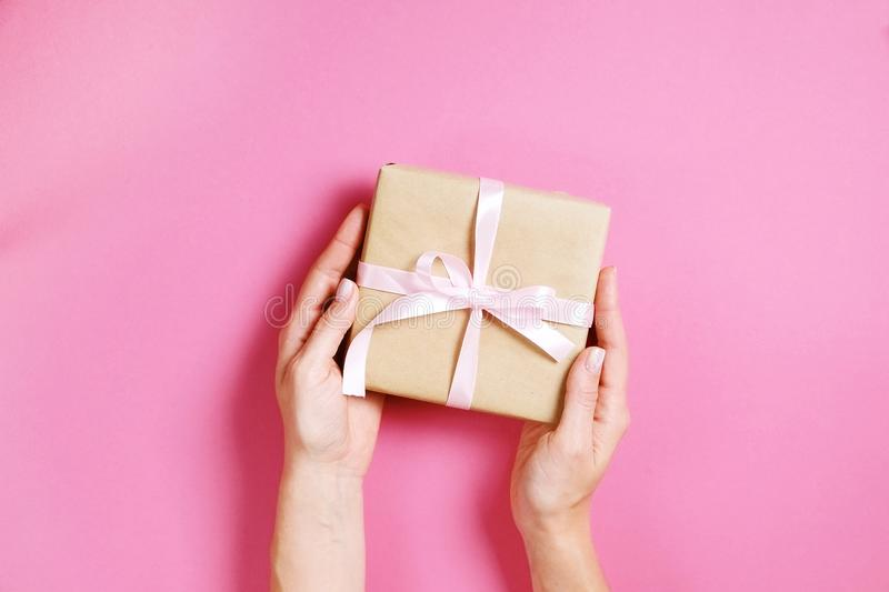 Close up of female hands holding birthday gift in vintage craft paper wrapping. Femenine composition with present in woman`s arms stock photos
