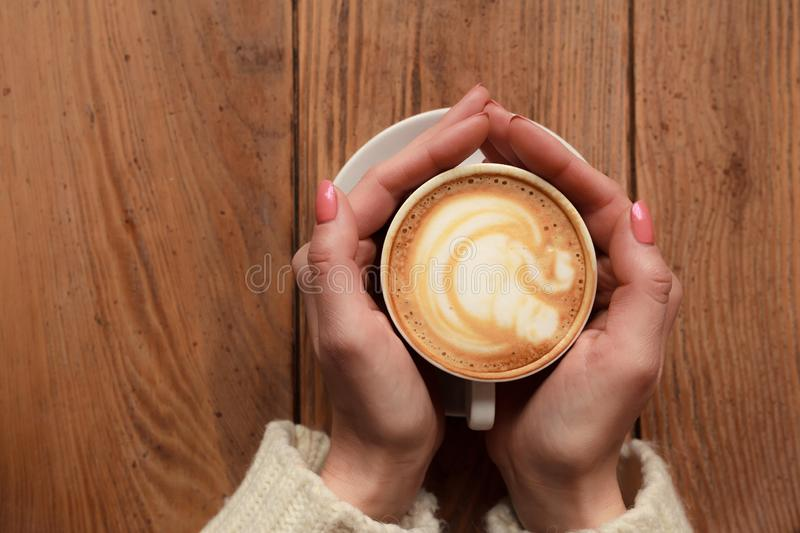 Close-up female hands holding cup with coffee cappuccino with foam with nice pattern. Perfect red gel polish manicure. Wood royalty free stock photo