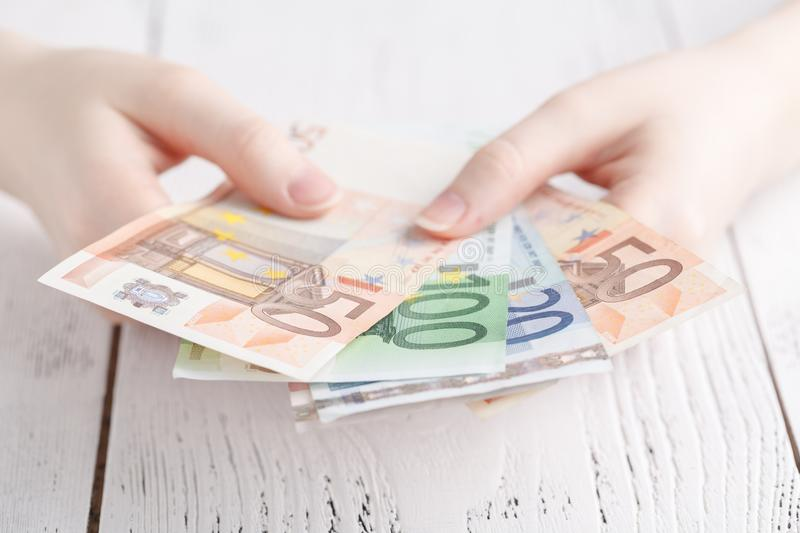 Close up female hands holding few euro banknotes royalty free stock photos