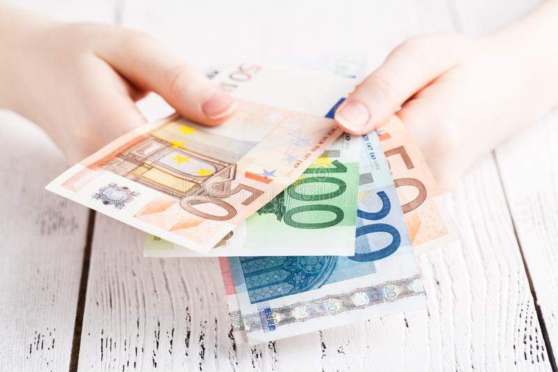 Close up female hands holding few euro banknotes stock photography