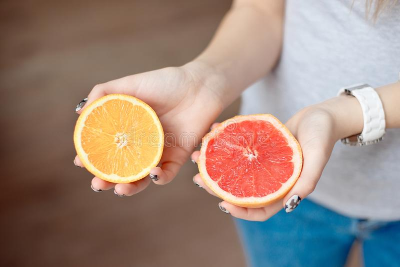 Orange and grapefruit in human`s hands. Close-up female hands holding two halves of sliced citrus fruit. Orange and grapefruit in human`s hands stock photo