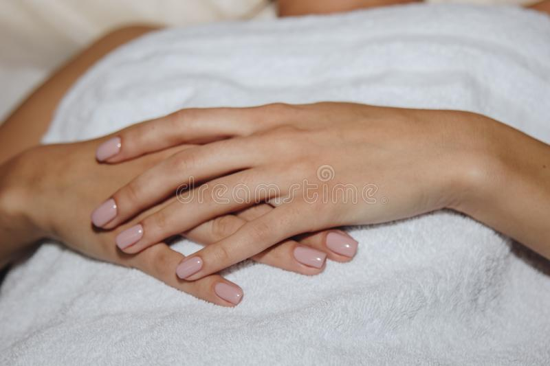 Close-up female hands lie on a white terry towel. preparation for spa treatments stock photo