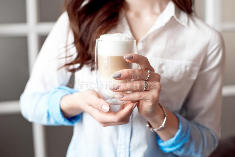 Close-up of female hands in office clothes holding a glass cup of coffee with soy milk during a break at work, lifestyle royalty free stock photography
