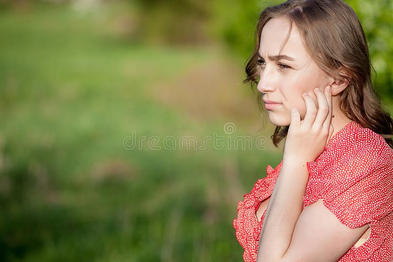 Close-up Of Female Hands Putting Hearing Aid In Ear. Modern digital in the ear hearing aid for deafness and the hard of hearing. Patients royalty free stock photography