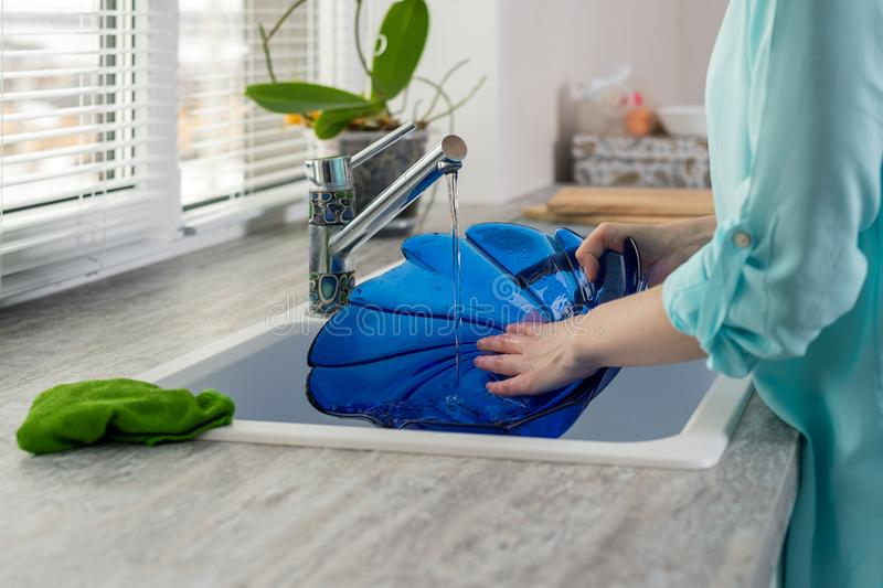 Close-up of female hands rinse blue plate under the pressure of water in the kitchen sink in front of the window royalty free stock image