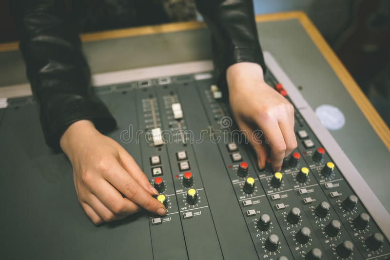 Close up of female hands turning up volume stock images